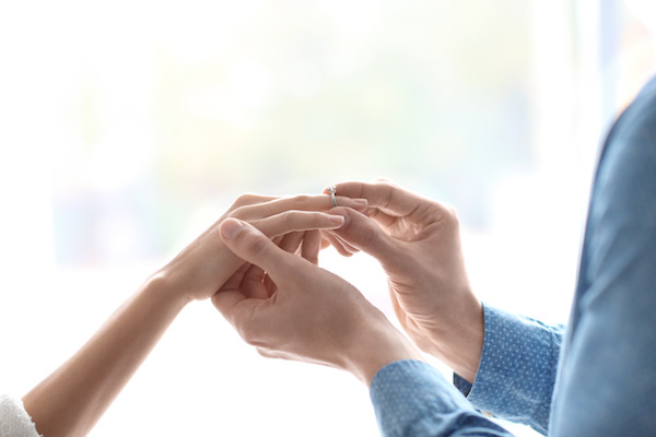Man putting beautiful engagement ring on his beloved, closeup