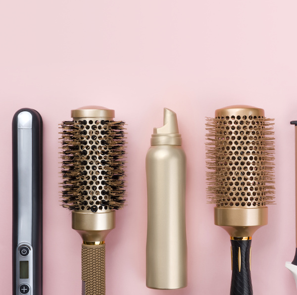 Professional hair dresser tools on pink background with copy space
