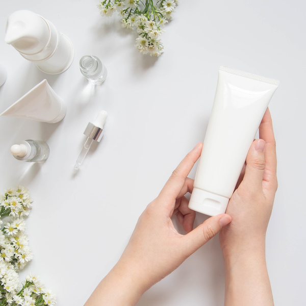 Young female hand holding blank white squeeze bottle plastic tube w/ organic natural skincare products and flower on white table. Packaging of lotion, cream or serum. Beauty cosmetic skincare concept.